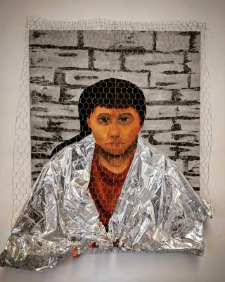 Hexagon-shaped wire placed in front of a canvas painting of a female in a dark orange shirt, with a metallic-colored thermal blanket positioned on top of the image so that it looks like it's around their shoulders and then trails down to the ground and then pops out underneath the left side of the wire. Behind the person is a background of painted gray-cemented bricks.