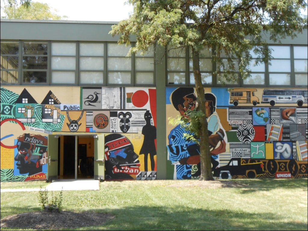 Wide view of a mural on the side of a building. On the right is the mural described above and on the left is a continuation of that mural with more grid-style images along with a silhouetted figure and two large black faces on either side of the building's door, facing away from the two sides of an open double door.