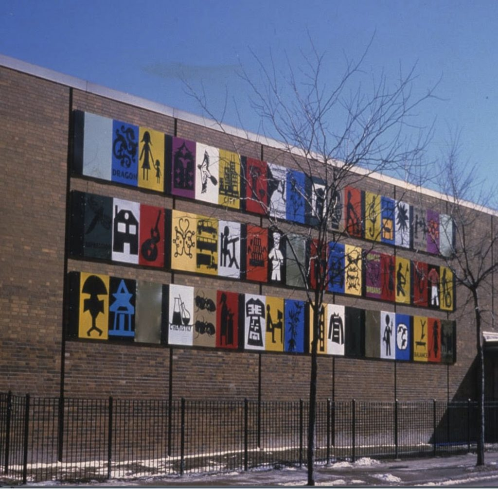 The side of a brick building with three separate rows of eighteen different color-blocked grid-style images including a dragon, a figure working at a desk, a house, and a skyscraper.