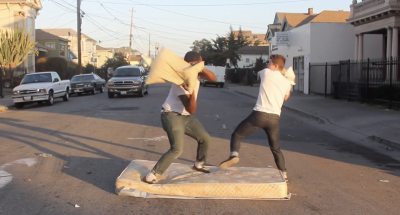 One Black man and one white man are engaged in a pillow fight in the center of an urban street. They are balanced on a tattered mattress as a vehicle drives toward them.