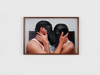 A photograph of two dark-skinned individuals kissing passionately in front of a white wall with their heads and faces covered by reversed black Du-Rags.