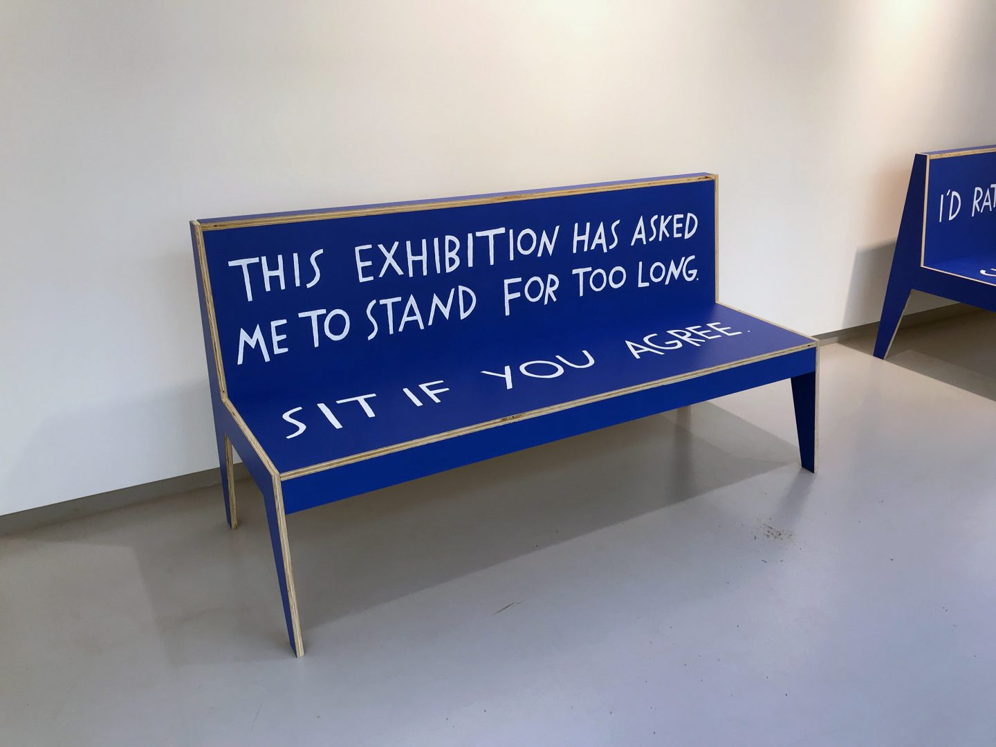 """Blue wooden bench in a gallery with text painted on it. The back of the bench reads, """"This exhibition has asked me to stand for too long."""" The seat reads, """"Sit if you agree."""""""
