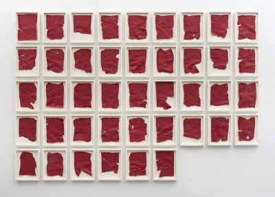 On a white wall, a number of lined up frames contain scraps of red fabric-like paper.