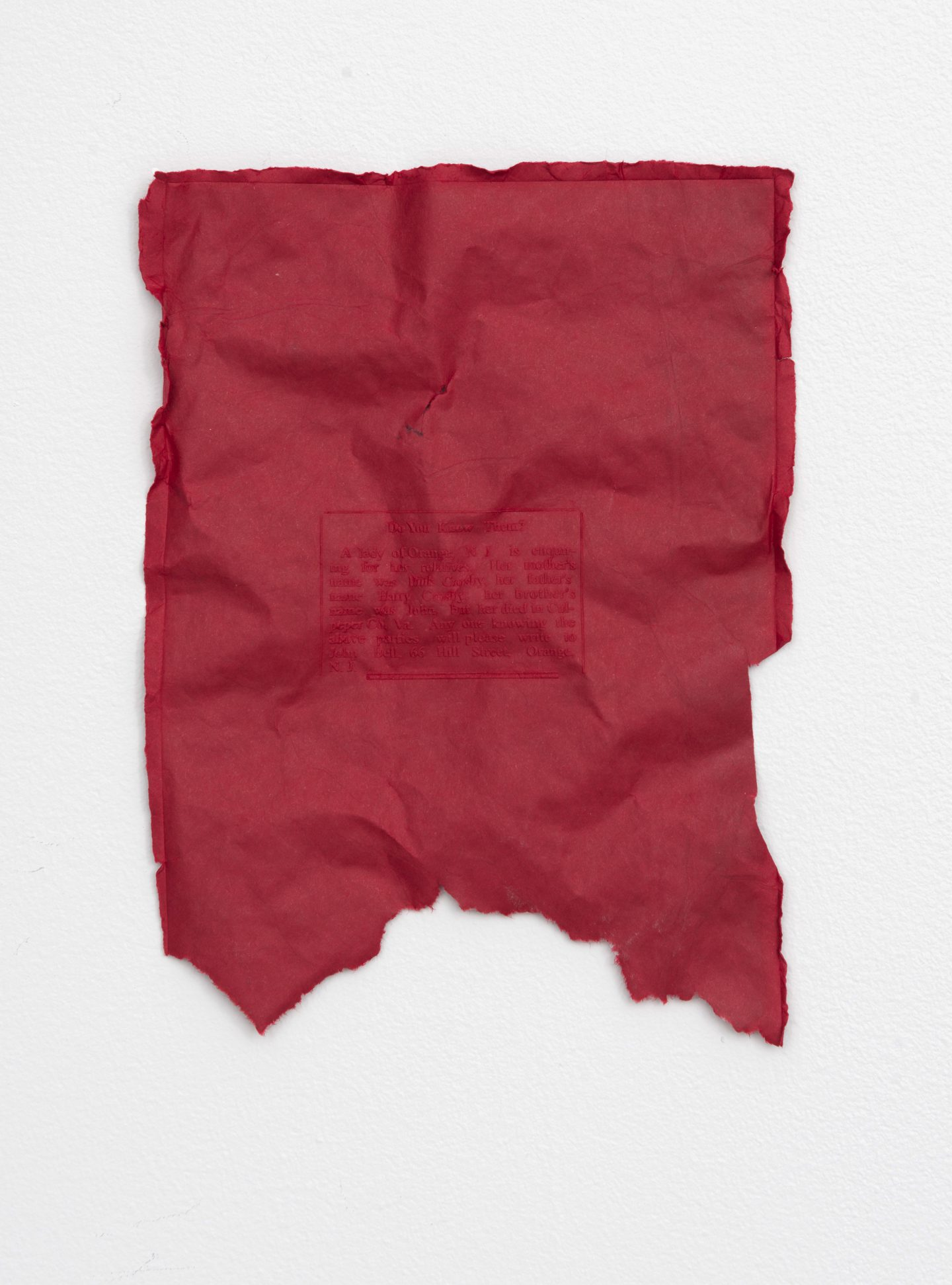 On a white wall, a single piece of crumpled and torn red paper.