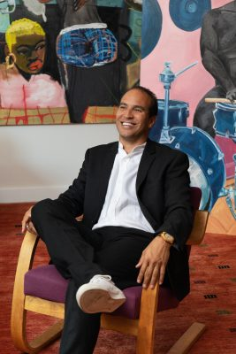 A black man in a suit sits in front of a contemporary art piece and smiles towards just off camera