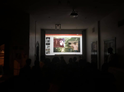 A dark room with a projected image on a screen.