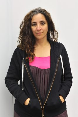 A woman with light brown skin and curly brown hair looks into the camera with a small smile.