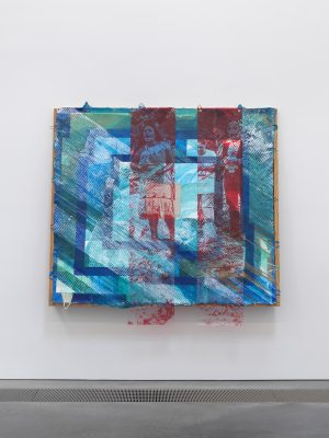 Mixed media artwork in blue and red on a white gallery wall.