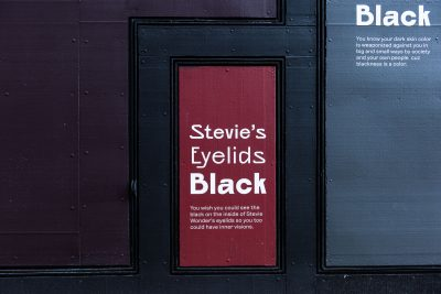Exterior building painted in shades of black. In the center panel, painted red, it reads,