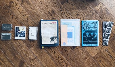On a wood floor, eight pieces of material culture, such as cassette tapes, zines, photo-booth strips, and polaroid pictures, sit in a row.