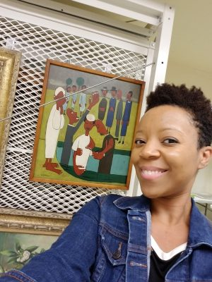 A black woman with short hair stands smiling in front of a painting.