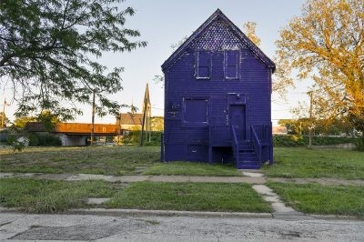 Blue house surrounded by grass and a concrete sidewalk.